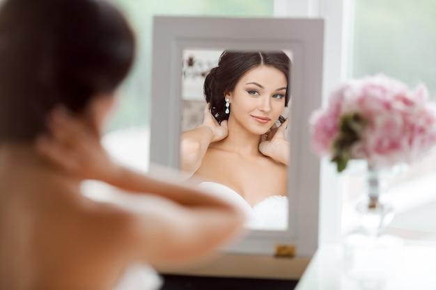 Portret młodej pięknej narzeczonej patrzy na siebie w lustrze
