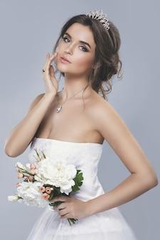 Portret młodej pięknej narzeczonej z bukietem kwiatów