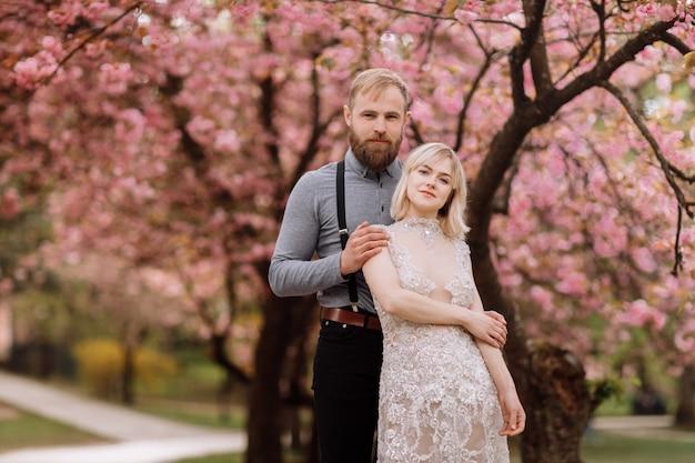 Portret młodej pięknej pary w kwitnących różowy kwiat wiśni, ogród sakura i przytulanie w słoneczny dzień. wiosenny portret ślubny. walentynki.