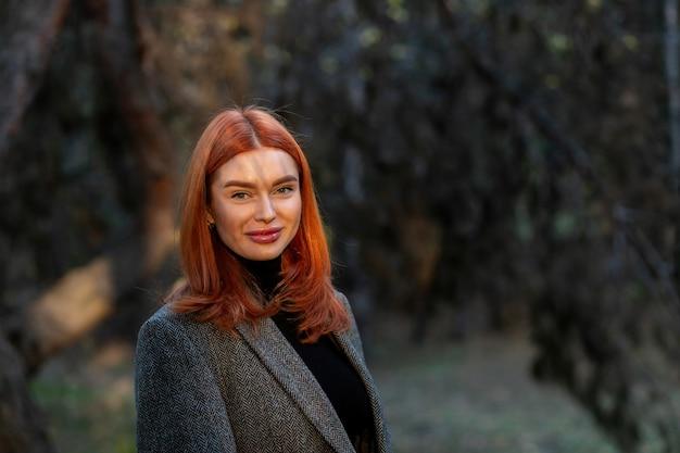 Portret młodej pięknej rudowłosej kobiety, na zewnątrz. dobry ciemny dzień z pięknymi cieniami słoneczny dzień, zachód słońca. samodzielna izolacja na świeżym powietrzu.