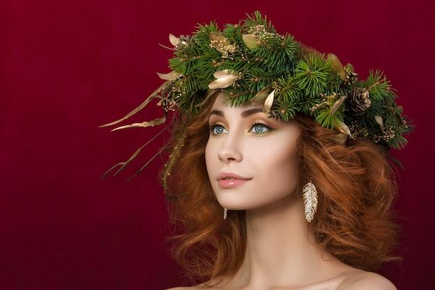 Portret młodej pięknej rudowłosej kobiety z jodłowym wieńcem ze złotymi liśćmi we włosach.