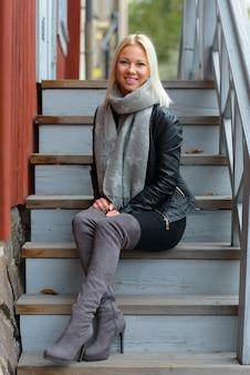 Portret młodej pięknej skandynawskiej blondynki kobiety przeciwko czerwony drewniany budynek na zewnątrz