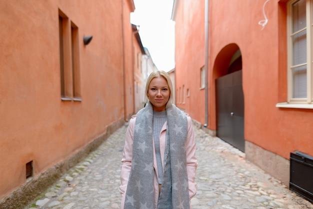 Portret młodej pięknej skandynawskiej blondynki kobiety wzdłuż alei z pomarańczowym budynkiem w mieście