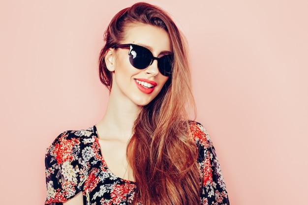 Portret młodej pięknej szczupłej kobiety w seksownej sukni z zmysłowymi ustami w noszeniu okularów przeciwsłonecznych, uśmiechając się i pozowanie