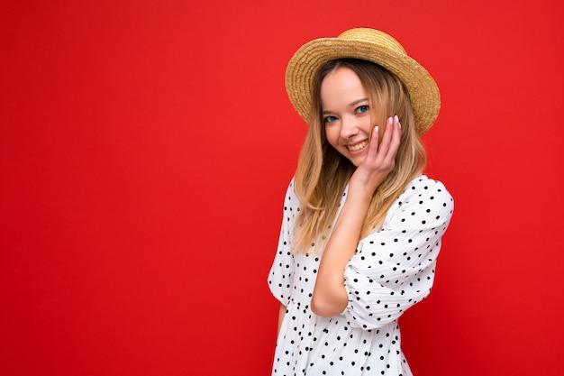 Portret młodej pięknej uśmiechający się hipster blondynki kobiety w modnej letniej sukience i słomkowym kapeluszu. seksowny