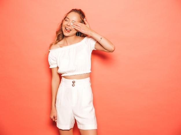 Portret młodej pięknej uśmiechający się hipster dziewczyny w modne letnie ubrania. seksowna beztroska kobieta pozuje blisko menchii ściany. pozytywny model zabawy. pokazuje język i zakrywa twarz dłonią