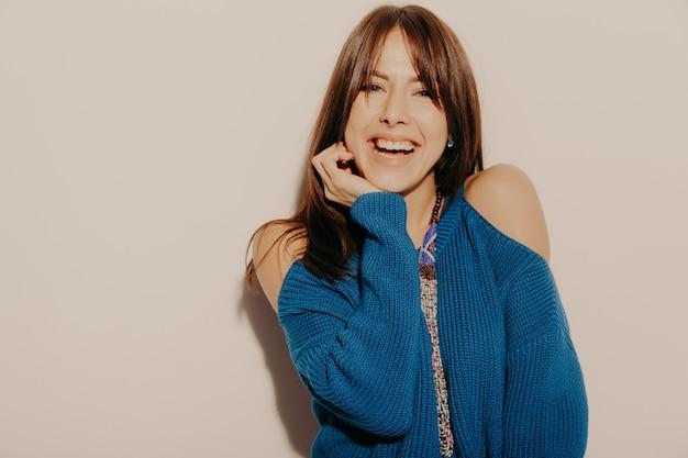 Portret młodej pięknej uśmiechający się hipster dziewczyny w modne letnie ubrania. seksowna beztroska kobieta pozuje blisko ściany w studiu. pozytywny model zabawy