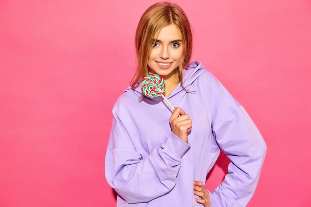 Portret młodej pięknej uśmiechający się hipster kobiety w modne letnie sweter z kapturem. seksowna beztroska kobieta pozuje blisko menchii ściany. pozytywny model z lollipopem