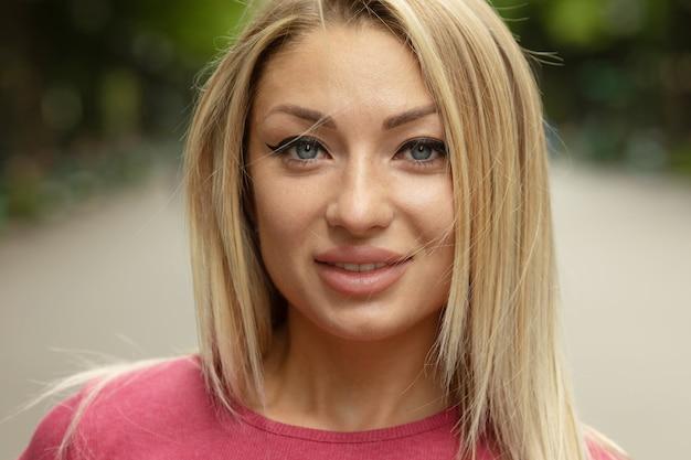 Portret młodej pięknej uśmiechnięta blondynka na zewnątrz