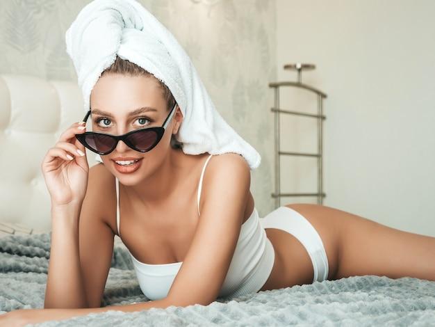 Portret młodej pięknej uśmiechniętej dziewczyny w białej bieliźnie i ręczniku na głowie