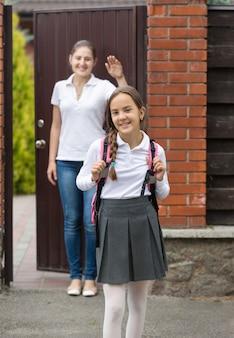 Portret młodej pięknej uśmiechniętej dziewczyny z torbą idzie do szkoły