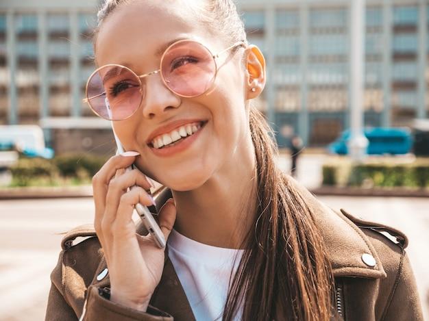 Portret młodej pięknej uśmiechniętej kobiety mówiąc na telefon modna dziewczyna w przypadkowych letnich ubraniach śmieszna i pozytywna kobieta pozuje na ulicy