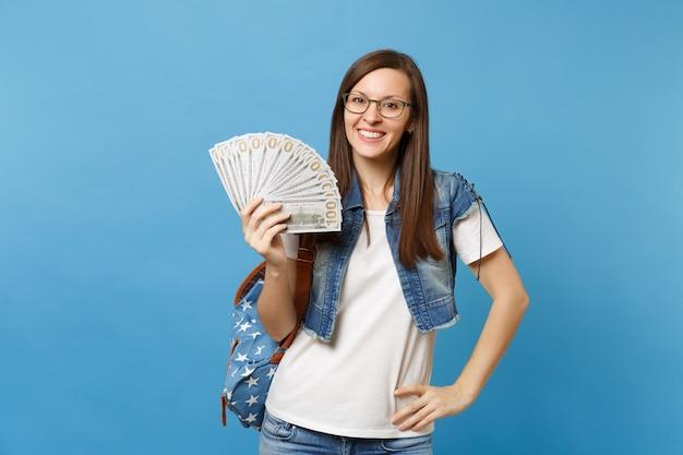 Portret młodej pięknej uśmiechniętej kobiety studenta w okularach z plecakiem trzymającym pakiet wiele dolarów, pieniądze w gotówce na białym tle na niebieskim tle. edukacja w koncepcji liceum uniwersyteckiego.