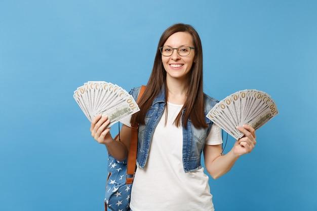 Portret młodej pięknej uśmiechniętej kobiety studentki w okularach z plecakiem trzymającym pakiet wiele dolarów, pieniądze w gotówce na białym tle na niebieskim tle. edukacja w koncepcji liceum uniwersyteckiego.