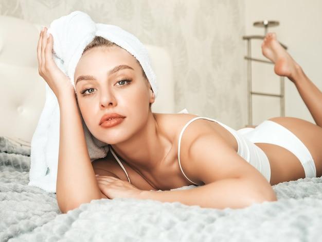 Portret młodej pięknej uśmiechniętej kobiety w białej bieliźnie i ręczniku na głowie