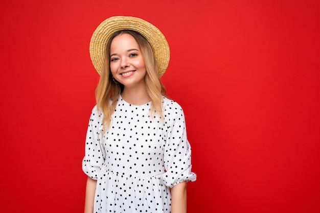 Portret młodej pięknej uśmiechniętej kobiety w modnej letniej sukience i słomkowym kapeluszu