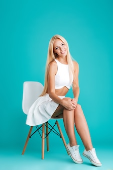 Portret młodej pięknej wesołej dziewczyny siedzącej na krześle na białym tle na niebieskim tle