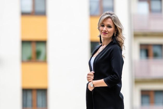 Portret młodej pozytywnej, eleganckiej kobiety biznesu na tle rozmytego miasta, kopia przestrzeń