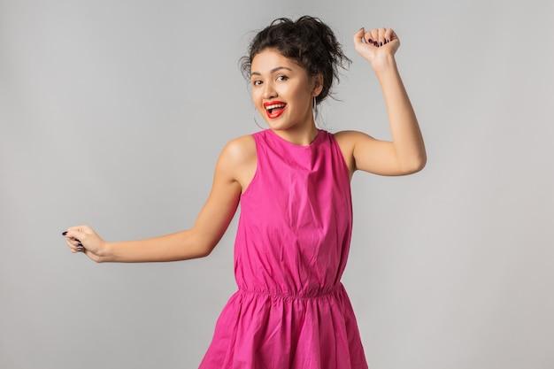 Portret młodej pozytywnej ładnej kobiety w różowej sukience, taniec, szczęśliwy, uśmiechnięty, letni styl, czerwona szminka, trend w modzie, zalotny, azjatycka, mieszana rasa, na białym tle