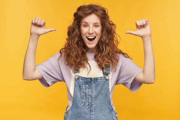 Portret młodej pozytywnej rudej kobiety, ubranej w niebieski kombinezon i fioletową koszulkę, uśmiecha się szeroko, dobrze się bawi, wskazując palcem na siebie odizolowaną na żółtej ścianie