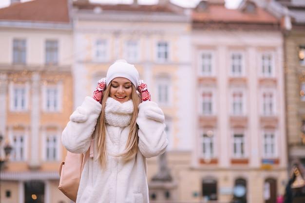 Portret młodej pozytywnej wesołej szczęśliwej kobiety o poranku na jarmark bożonarodzeniowy.