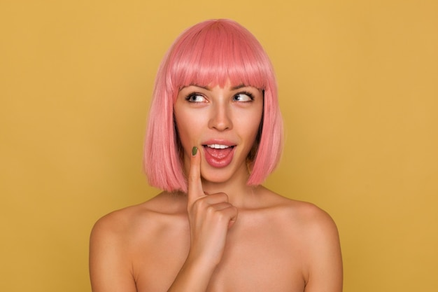 Portret młodej pozytywnej zamyślonej niebieskookiej różowowłosej pani z naturalnym makijażem, trzymając palec wskazujący na twarzy, patrząc wesoło na bok, odizolowaną na musztardowej ścianie