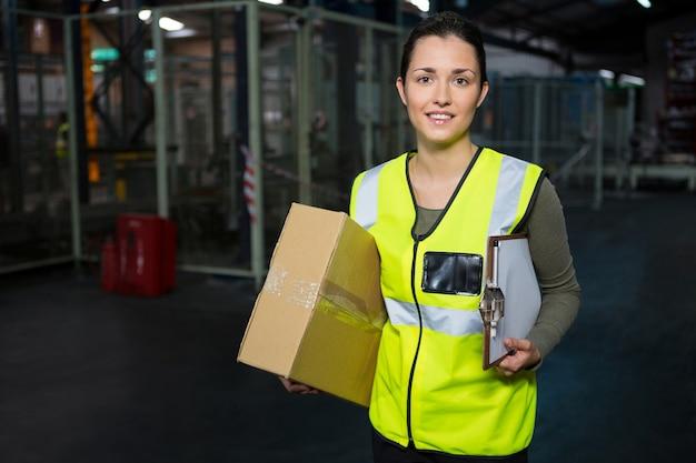 Portret młodej pracownica stojąca w magazynie