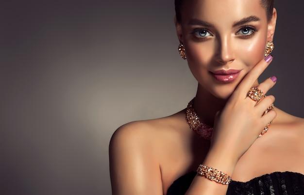 Portret młodej, przepięknej kobiety ubranej w wspaniały makijaż z długimi czarnymi rzęsami i ciemnoróżową szminką piękna modelka ubrana w modny komplet biżuterii