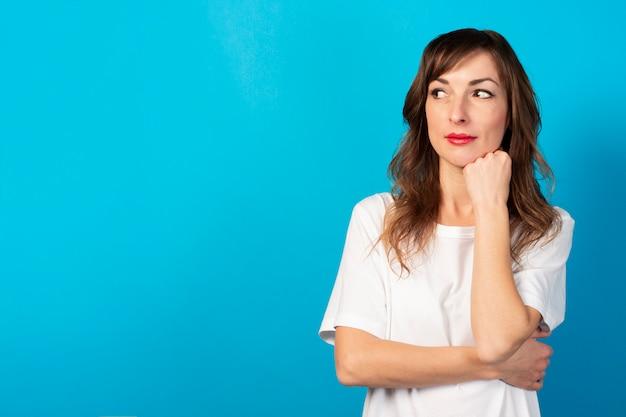 Portret młodej przyjaznej kobiety w swobodnej koszulce trzyma ręce pod brodą i odwraca wzrok na niebiesko