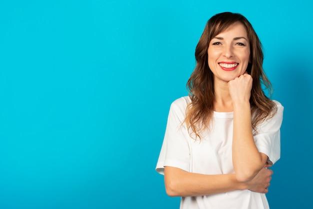Portret młodej przyjaznej kobiety w swobodnej koszulce trzyma ręce pod brodą i uśmiecha się na niebiesko