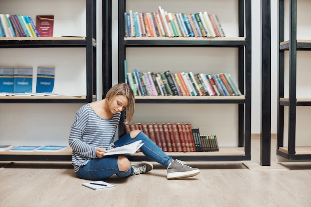 Portret młodej przystojnej studentki z krótkimi blond włosami w swobodnych stylowych ubraniach siedzącej na podłodze w nowoczesnej bibliotece przy półkach, czytającej ulubione książki, spędzającej weekend w przytulnej atmosferze