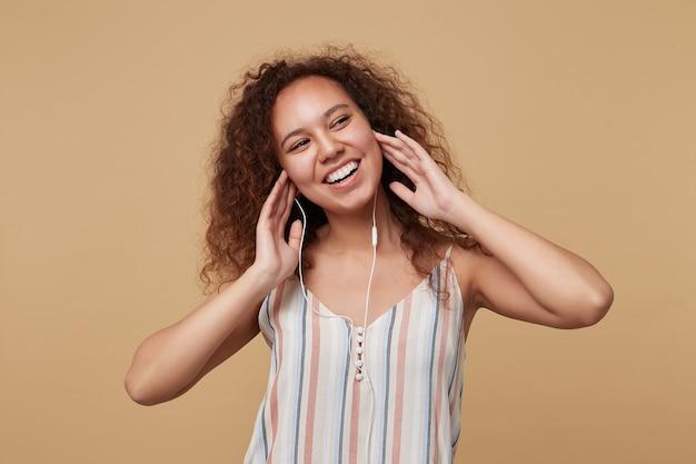 Portret młodej radosnej brązowowłosej kręconej kobiety trzymającej uniesione ręce na słuchawkach i uśmiechającej się wesoło, pozującej na beżu w pasiastym topie
