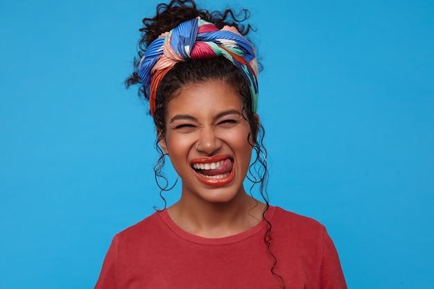 Portret młodej radosnej ciemnowłosej pani z kolczykiem w nosie mrużąc oczy i pokazując wesoło język, stojąc nad niebieską ścianą w kolorowych ubraniach