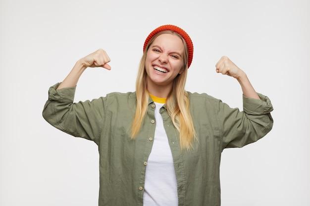 Portret młodej radosnej, długowłosej blondynki, marszczącej brwi radośnie twarz i trzymającej ręce uniesione, pozującej na niebiesko w codziennych ubraniach i czerwonym kapeluszu