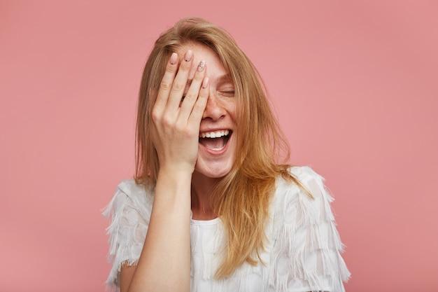 Portret młodej radosnej rudowłosej kobiety z naturalnym makijażem trzymającej dłoń na twarzy i uśmiechającej się wesoło z zamkniętymi oczami, stojąc na różowym tle