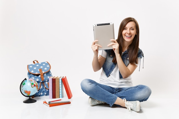 Portret młodej radosnej studentki w dżinsowych ubraniach, trzymającej komputer typu tablet pc, siedzącej w pobliżu kuli ziemskiej, plecaka, podręczników szkolnych