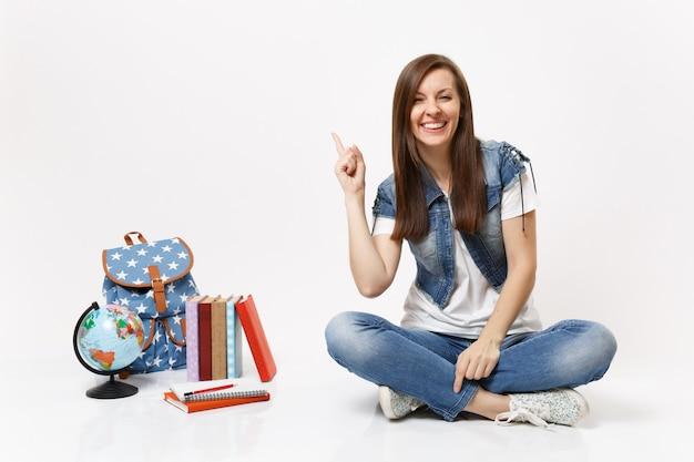 Portret młodej radosnej studentki w dżinsowych ubraniach wskazujący palec wskazujący w górę, siedzący w pobliżu kuli ziemskiej, plecaka, podręczników szkolnych na białym tle