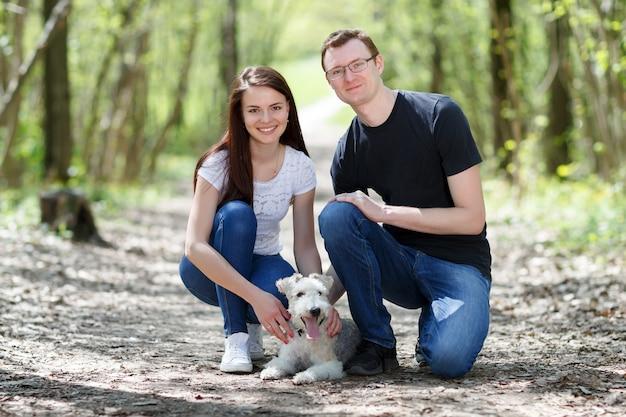 Portret młodej rodziny z psem w parku