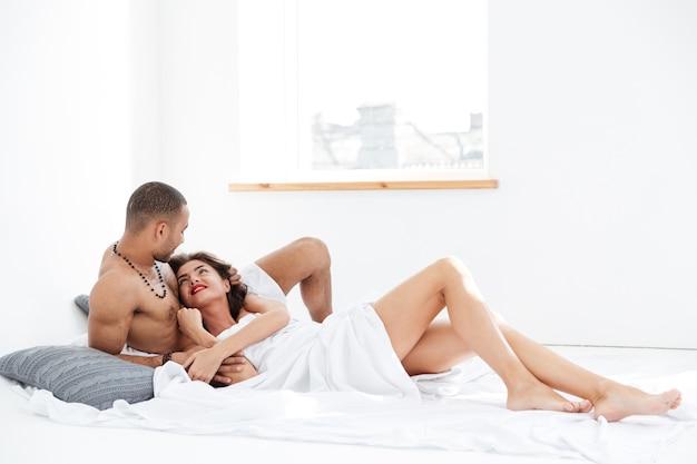 Portret młodej romantycznej pary przytulającej się i całującej, leżącej na białym łóżku