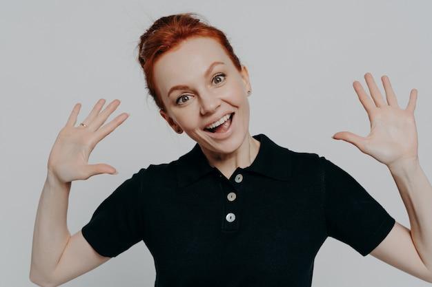 Portret młodej rozbawionej rudej kobiety podnoszącej dłonie i patrzącej na kamerę z radosnym wyrazem twarzy, podekscytowana ruda kobieta widząc coś śmiesznego, ubrana w czarną koszulkę, na białym tle na szarym tle