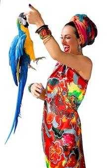 Portret młodej roześmianej atrakcyjnej kobiety w afrykańskim stylu z papugą ara na palcu