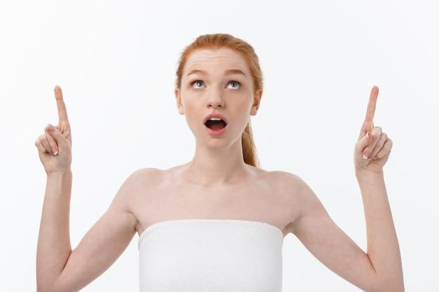 Portret młodej rudowłosej kobiety z doskonałą piegowatą skórą pokazano