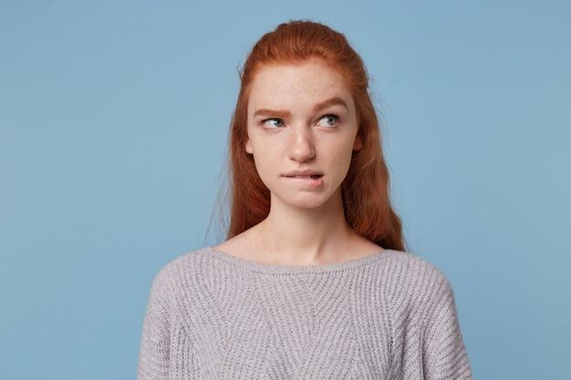 Portret młodej rudowłosej nastolatki odwraca wzrok przygryzł dolną wargę