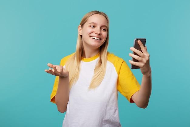 Portret młodej siwowłosej kobiety z naturalnym makijażem, uśmiechającej się radośnie podczas rozmowy wideo, ubrana w ubranie pozując na niebiesko