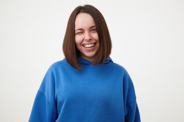 Portret młodej ślicznej brunetki kobiety bez makijażu, mrugając radośnie do przodu i uśmiechając się szeroko, stojąc nad białą ścianą