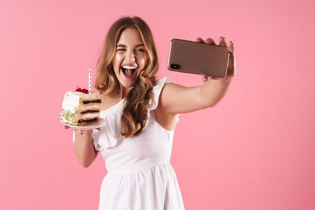 Portret młodej śmiejącej się kobiety biorącej selfie portret na telefonie komórkowym i mrugający, trzymając kawałek ciasta ze świecą odizolowaną na różowej ścianie