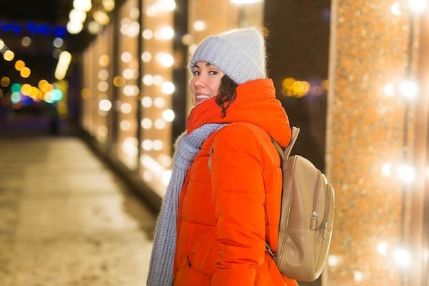 Portret młodej śmiesznej atrakcyjnej kobiety na śnieżnym tle bożego narodzenia. ferie zimowe i koncepcja sezonu.