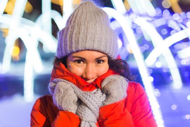 Portret młodej śmiesznej atrakcyjnej kobiety na śnieżnym tle bożego narodzenia ferie zimowe i sezon