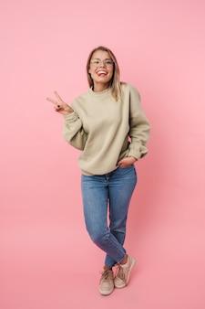 Portret młodej śmiesznej kobiety w okularach gestykulującej znak pokoju i wysuwającej język na białym tle nad różową ścianą