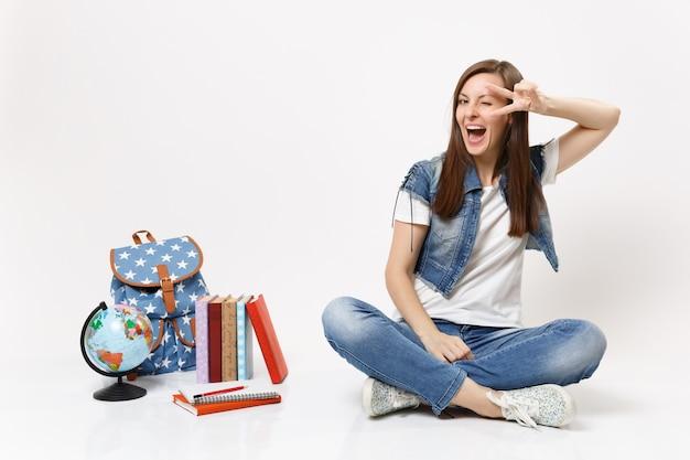 Portret Młodej śmiesznej Radosnej Kobiety Studentki W Dżinsowych Ubraniach Pokazujących Znak Zwycięstwa Siedzącej W Pobliżu Kuli Ziemskiej, Plecaka, Podręczników Szkolnych Premium Zdjęcia
